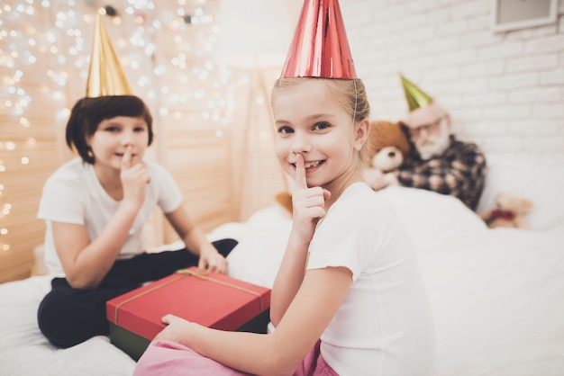 Os miúdos impertinentes abrem o gesto de silêncio do presente de aniversário.