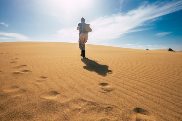 Os mochileiros exploram e aventuram o conceito de atividade de lazer com um homem caminhando nas dunas do deserto com uma mochila