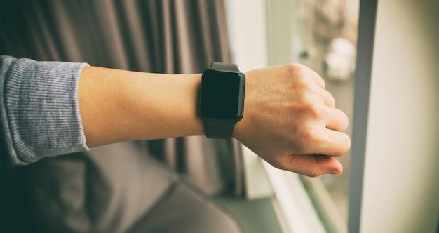 Os modernos relógios inteligentes na mão da mulher