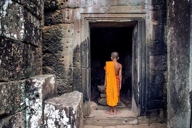 Os monges nas antigas faces de pedra do templo de bayon, angkor wat, siam reap, camboja