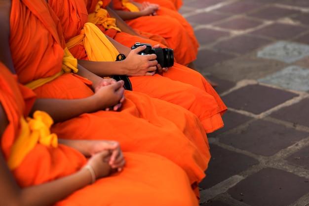 Os monges sentam-se em ordem. e tem uma câmera por perto