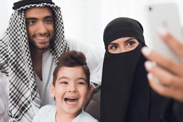 Os muçulmanos sentam em casa e tiram uma selfie no telefone.