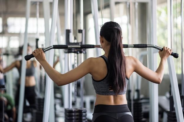 Os músculos traseiros da bomba da mulher exercitam no gym