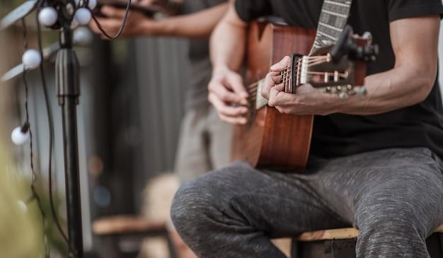 Os músicos estão checando o som do violão e tentando tocar violão antes do evento