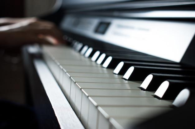Os músicos tocam piano na sala de prática de música.