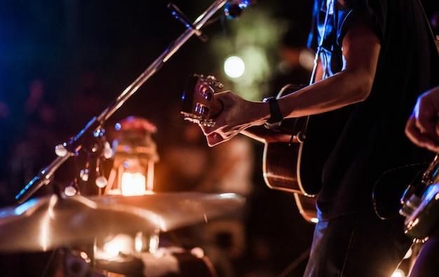 Os músicos tocavam rock no palco e havia uma plateia cheia de gente assistindo