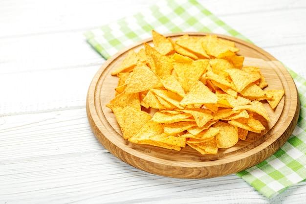 Os nachos mexicanos picantes lascam-se em uma bandeja de madeira.