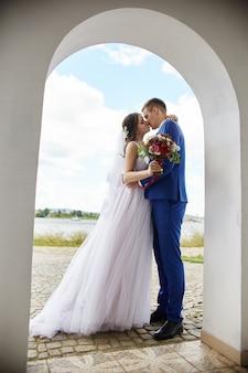 Os noivos abraçam e beijam o casamento