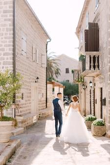 Os noivos caminham por uma rua estreita e aconchegante do centro histórico de perast de mãos dadas
