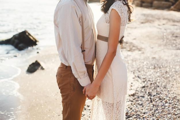 Os noivos de mãos dadas na praia. pôr do sol.