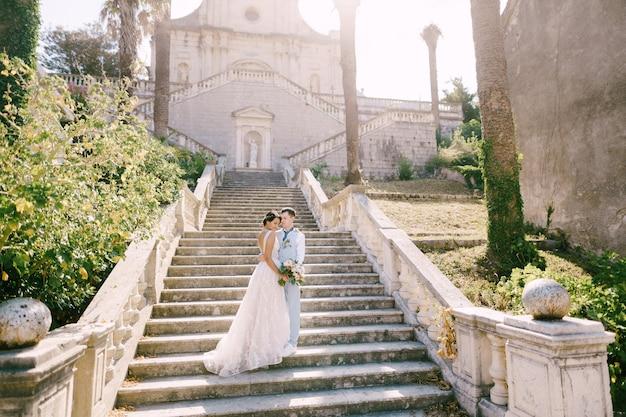 Os noivos estão abraçados nas escadas do presépio da bendita igreja da virgem maria em