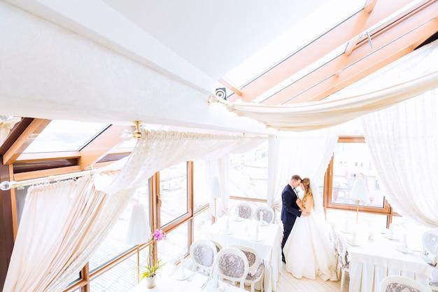 Os noivos estão se abraçando no salão do restaurante com o perfil do belo interior do salão