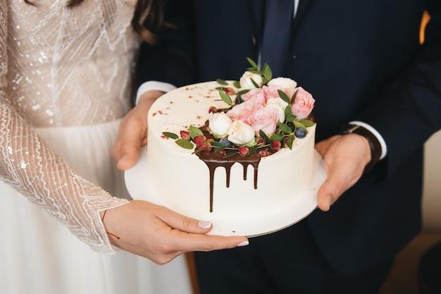 Os noivos estão segurando um pequeno bolo de casamento decorado com chocolate e flores