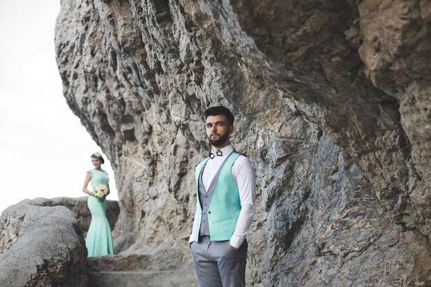 Os noivos na natureza nas montanhas perto da água. terno e vestido cor tiffany. o noivo olha para longe.