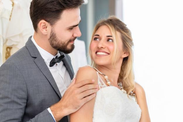 Os noivos pares de sorriso caucasiano e abraçam no estúdio do casamento.