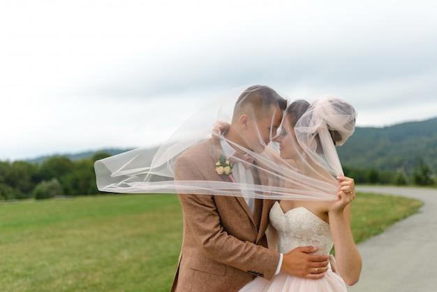 Os noivos se abraçam sob um véu e gentilmente inclinam a cabeça um para o outro.