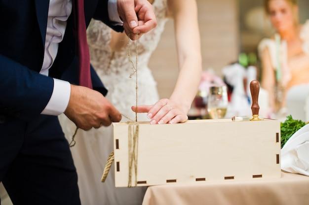 Os noivos selam uma garrafa de vinho no banquete de casamento.