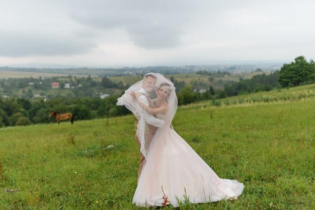 Os noivos sorriem e abraçam gentilmente sob um véu. o casal está olhando