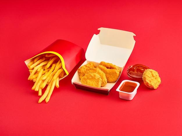 Os nuggets de frango e as batatas fritas no fundo vermelho