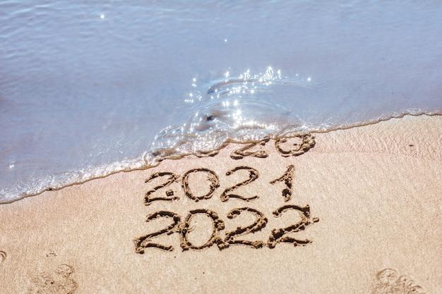Os números 2021, 2022 são desenhados na areia e levados pela onda, o símbolo do ano novo, a mudança do ano, o calendário