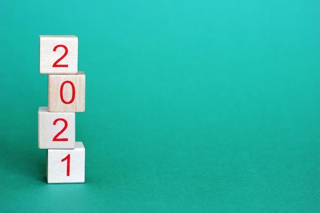 Os números 2021 estão em blocos de madeira que estão em uma pirâmide em cima uns dos outros em um verde