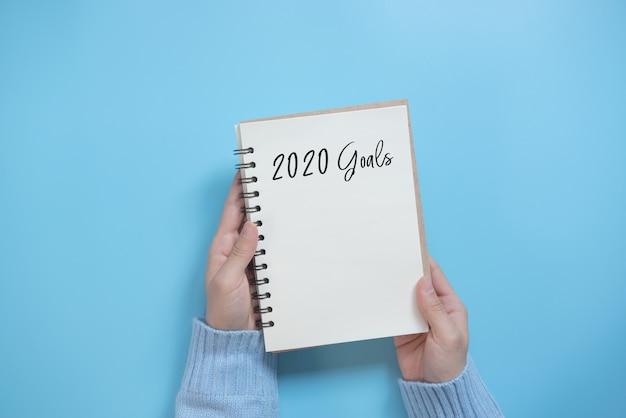 Os objetivos do ano novo 2020 listam com o caderno no fundo azul, estilo liso da configuração. conceito de planejamento.