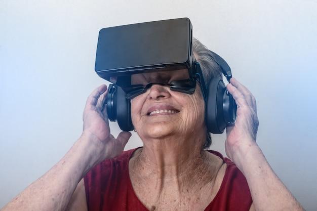 Os óculos de proteção modernos do uso feliz da avó vr cobrem no fundo branco. novas tendências e conceito de tecnologia e idosos ativos engraçados.