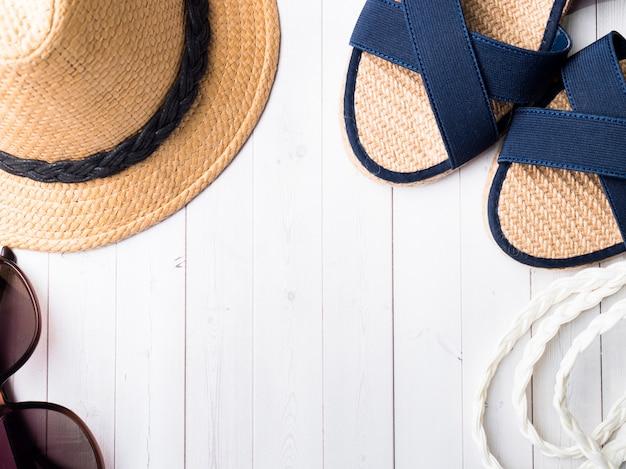 Os óculos de sol das sandálias dos braceletes do chapéu de palha do fundo do verão em uma tabela branca copiam o espaço.
