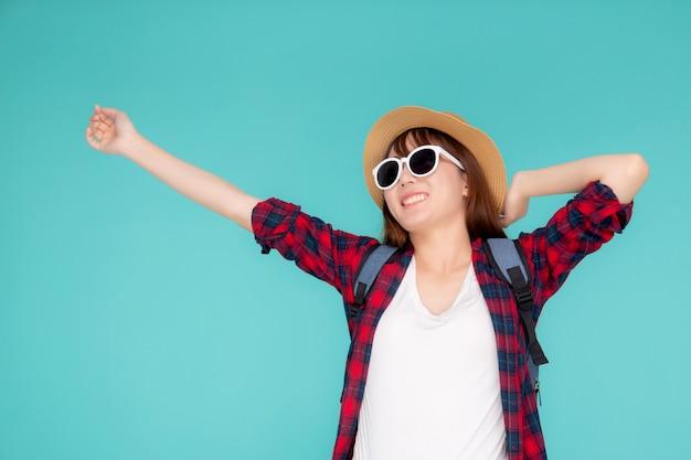 Os óculos de sol e o chapéu asiáticos novos bonitos do desgaste de mulher do retrato sorriem entusiasmado e confiantes apreciam o fundo azul isolado nas férias de verão.