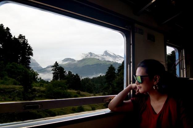 Os óculos de sol vestindo da mulher asiática bonita viajam pelo trem que olha através da janela do trem.