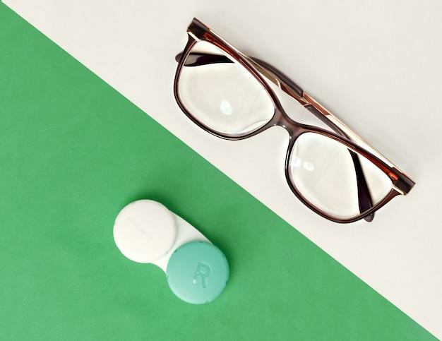Os óculos e as lentes de contato são brancos e verdes.