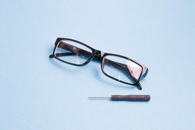 Os óculos em uma moldura de plástico preta e uma pequena chave de fenda estão em uma superfície azul clara