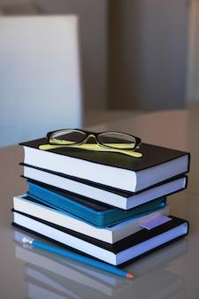 Os óculos estão em uma pilha de livros, ao lado de um lápis.