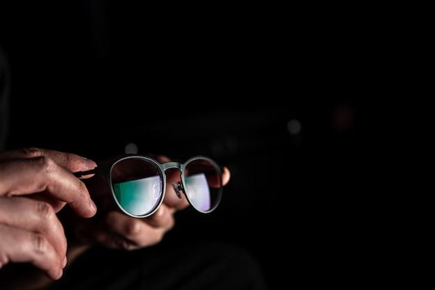 Os óculos nas mãos do homem refletem a luz da tela no escuro, espaço de cópia.
