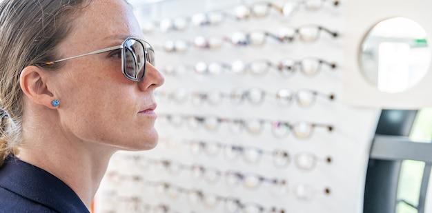 Os óculos são selecionados e testados por uma mulher em uma loja de óptica