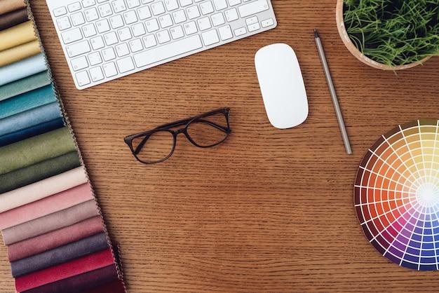 Os óculos, teclado, amostras de cores e mouse sobre a mesa.