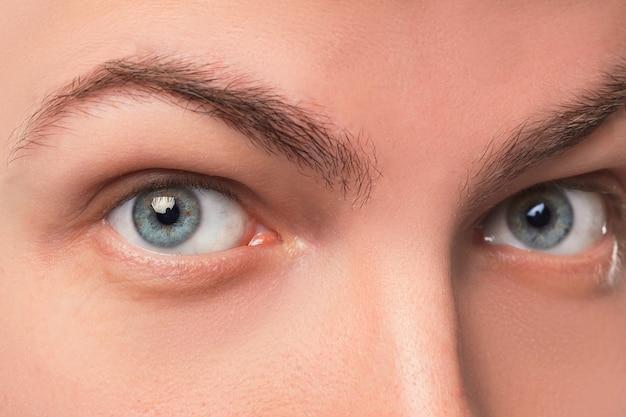 Os olhos azuis bonitos do homem fecham-se acima