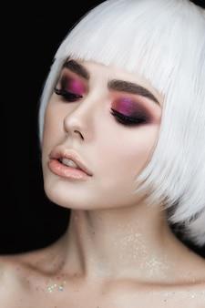 Os olhos fumarentos fazem a mulher loura nova bonita da composição com penteado do volume.