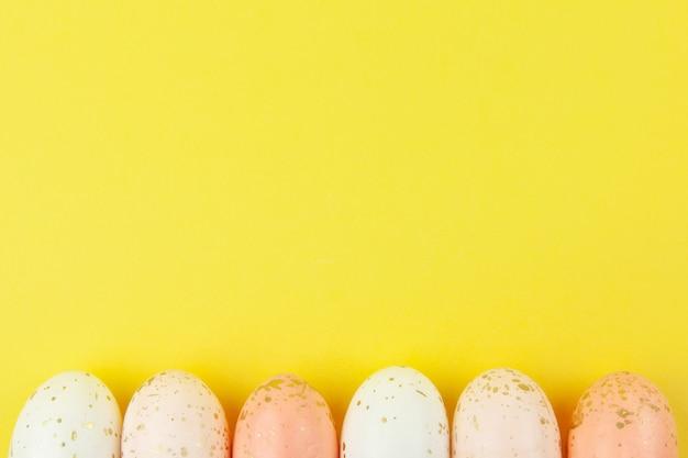 Os ovos criativamente pintados em tons pastel decorados com folha de ouro são dispostos em linha ao longo da borda inferior em fundo amarelo, copie o espaço.