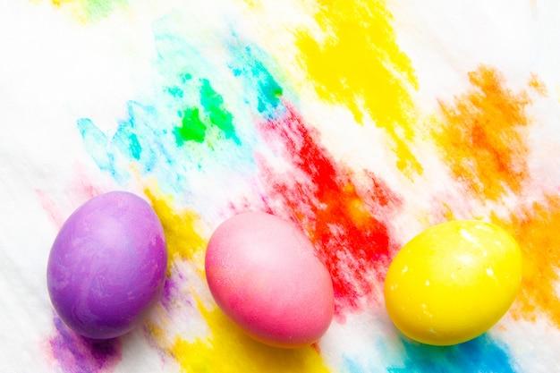 Os ovos da páscoa coloridos moldam a beira no fundo pintado multicolorido. vista de cima, copyspace