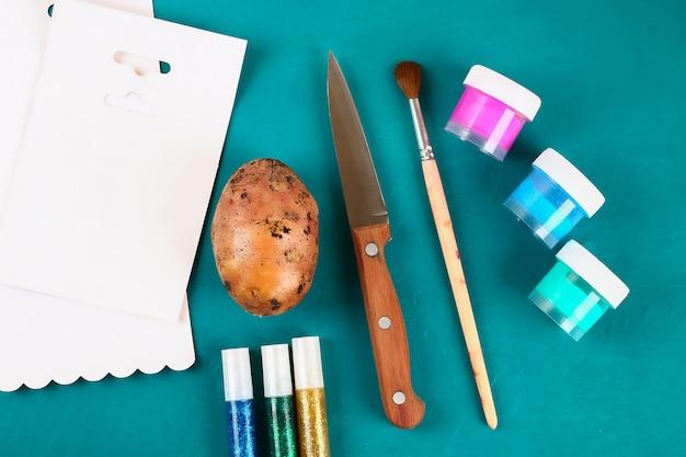 Os ovos da páscoa de diy feitos do cartão e a batata carimbam, cartão da páscoa no fundo verde.