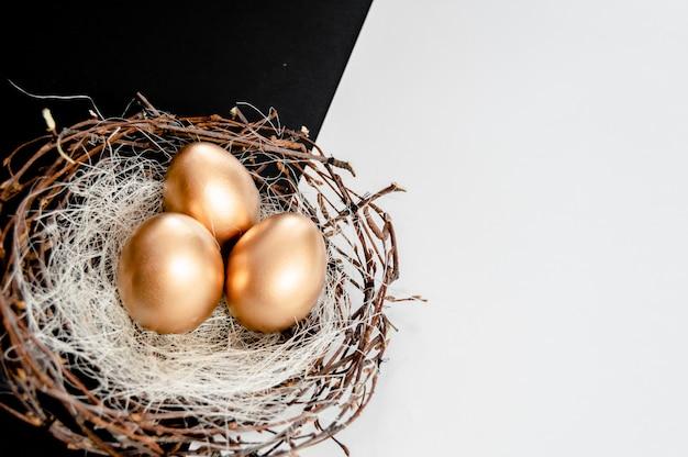 Os ovos da páscoa dourados nos pássaros aninham-se no fundo abstrato preto e branco.