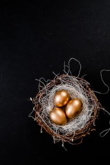 Os ovos da páscoa dourados nos pássaros aninham-se no fundo preto. opinião superior do copyspace do fundo do sumário do conceito do feriado da páscoa diversos objetos.
