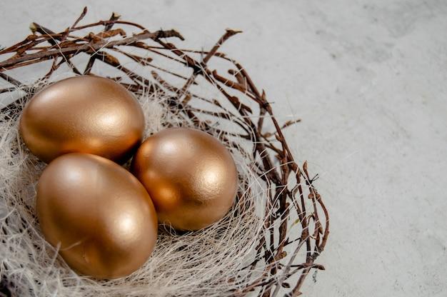 Os ovos da páscoa dourados nos pássaros aninham-se sobre o fundo rústico. férias de páscoa conceito abstrato fundo copyspace vista superior vários objetos.close para cima vista