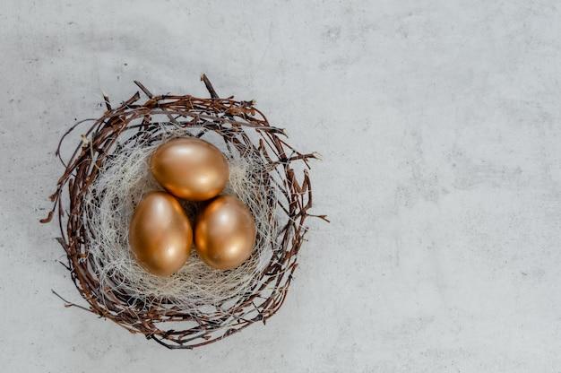 Os ovos da páscoa dourados nos pássaros aninham-se sobre o fundo rústico. opinião superior do copyspace do fundo do sumário do conceito do feriado da páscoa diversos objetos.