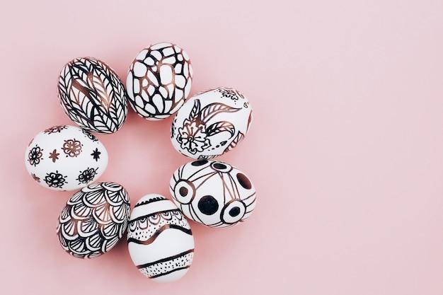Os ovos de páscoa são pintados em preto e branco, abstração, dispostos em círculo. ovos de páscoa pintados em um fundo rosa. postura plana. copie o espaço.