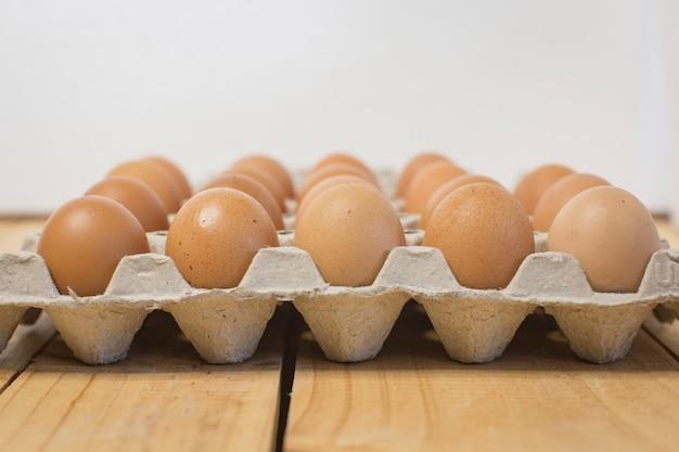Os ovos frescos e novos da galinha estão na tabela de madeira.
