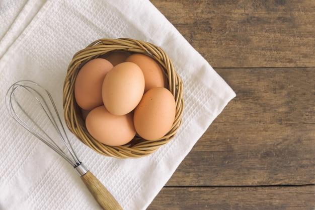 Os ovos frescos na cesta de madeira velha preparam-se cozinhando ou padaria na tabela de madeira rústica de madeira.