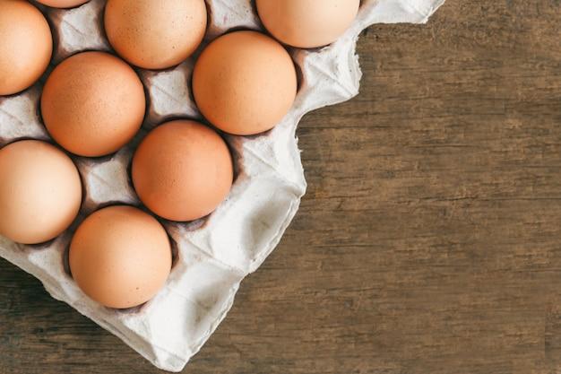 Os ovos frescos na cremalheira de ovo puseram na tabela de madeira. prepare ovos de galinha para cozinhar ou padaria.