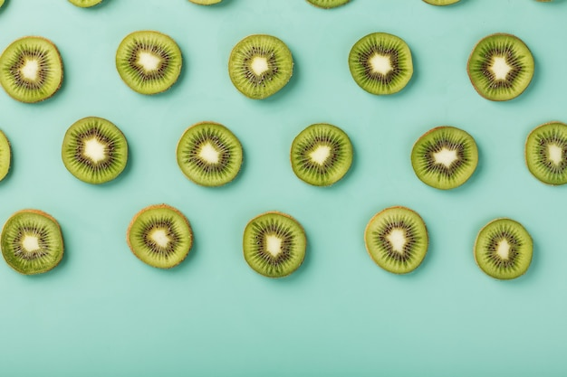 Os padrões das fatias de kiwis em fundo verde como um fundo contínuo.